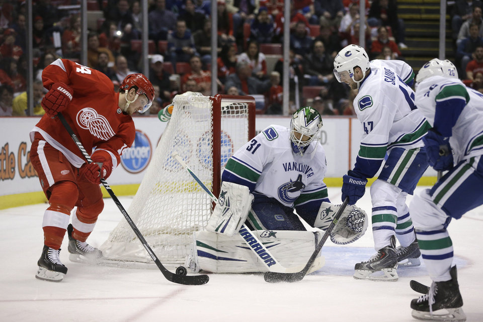 Photo - Detroit Red Wings center Gustav Nyquist (14) of Sweden controls the puck next to Vancouver Canucks goalie Eddie Lack (31) during the second period of an NHL hockey game in Detroit, Monday, Feb. 3, 2014. (AP Photo/Carlos Osorio)