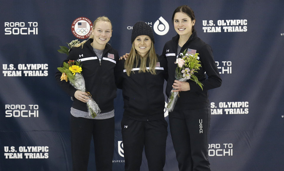 Photo - From left to right, second-place finisher Emily Scott, first-place finisher Jessica Smith and third-place finisher Alyson Dudek celebrate on the podium after the women's 500 meters during the U.S. Olympic short track speedskating trials on Saturday, Jan. 4, 2014, in Kearns, Utah. (AP Photo/Rick Bowmer)