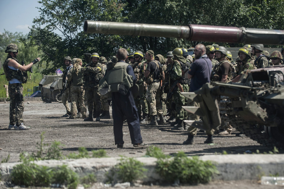 Photo - Ukrainian troops stand at a checkpoint near Slovyansk, eastern Ukraine, Saturday, July 5, 2014. Ukraine's forces claimed a significant success against pro-Russian insurgents on Saturday, chasing them from one of their strongholds in the embattled east of the country. Rebels fleeing from the city of Slovyansk vowed to regroup elsewhere and fight on.  (AP Photo/Evgeniy Maloletka)