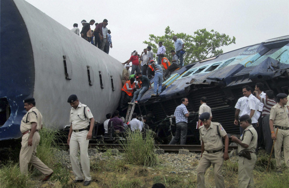 Indian officials and rescuers gather around the wreckage after the Gorakhpur Express passenger train slammed into a parked freight train Chureb, near Basti, Uttar Pradesh state,, India, Monday, May 26, 2014. According to officials dozens were killed. (AP Photo)