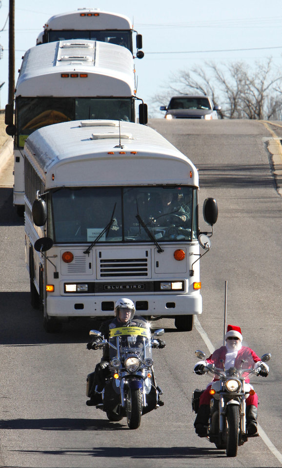 Photo - Left: Members of the Patriot Guard Riders escort soldiers riding in buses as they travel around Oklahoma City.