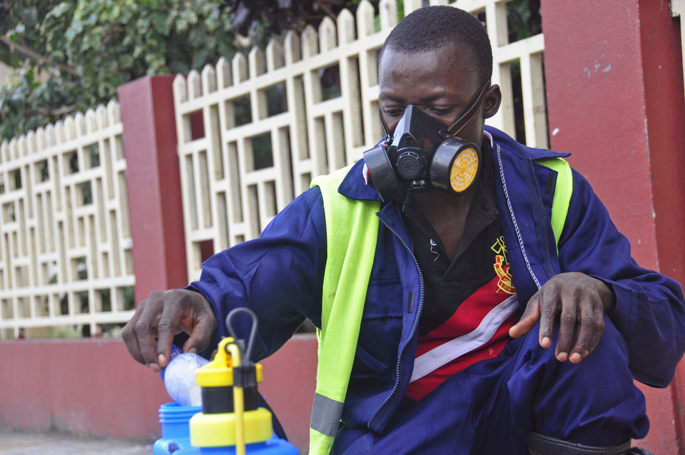 Photo - An employee  of the Monrovia City Corporation mixes disinfectant before spraying it on the streets in a bid to prevent the spread of  the deadly Ebola virus, in the city of Monrovia, Liberia, Friday, Aug. 1, 2014. U.S. health officials warned Americans not to travel to the three West African countries hit by the worst recorded Ebola outbreak in history. The travel advisory issued Thursday applies to nonessential travel to Guinea, Liberia and Sierra Leone, where the deadly disease has killed more than 700 people this year. (AP Photo/Abbas Dulleh)