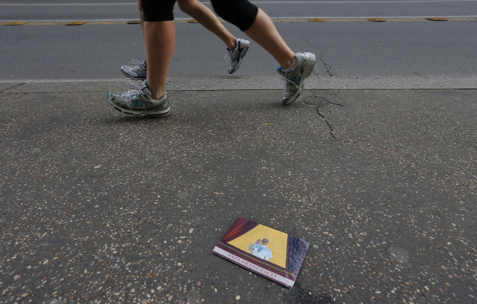 Runners go past a post card of newly elected Pope Francis on a sidewalk before the start of the Rome Marathon in Rome, Sunday, March 17, 2013. (AP Photo/Dmitry Lovetsky)