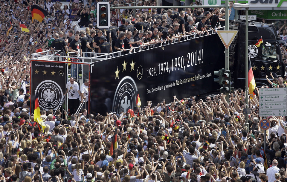 """Photo - Members of the German soccer squad wave to fans after  the arrival of the German national soccer team in Berlin Tuesday, July 15, 2014. Germany's World Cup-winning team has returned home  from Brazil to celebrate the country's fourth title with huge crowds of fans. The team's Boeing 747 touched down at Berlin's Tegel airport midmorning Tuesday after flying a lap of honor over the """"fan mile"""" in front of the landmark Brandenburg Gate.  (AP Photo/Michael Sohn)"""