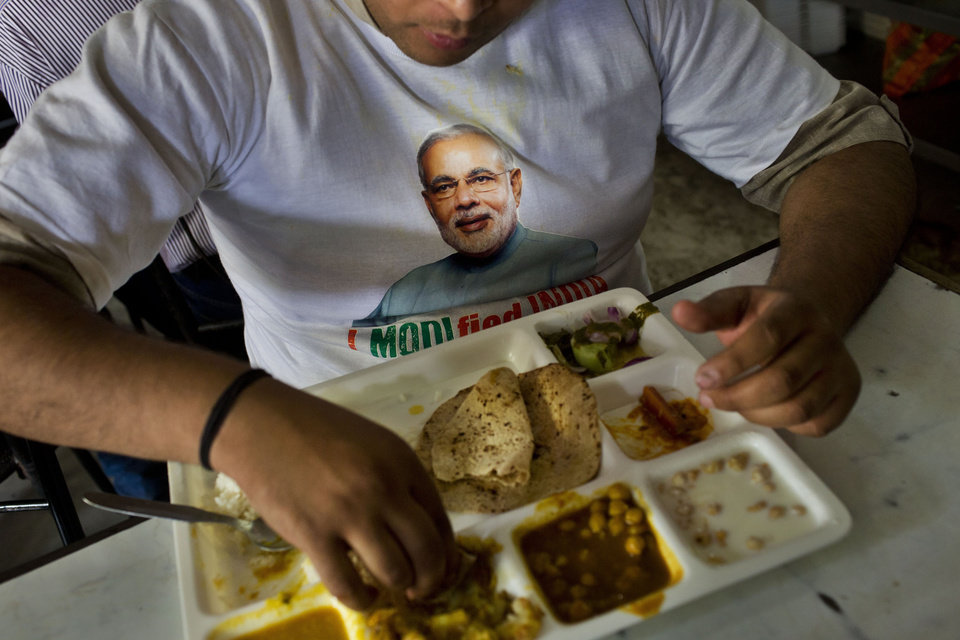 Photo - A supporter wears a t-shirt with a portrait of Bharatiya Janata Party (BJP) leader and India's next prime minister Narendra Modi and eats a meal at the canteen of the BJP party office in New Delhi, Friday, May 16, 2014. Modi and his party won national elections in a landslide Friday, preliminary results showed, driving the long-dominant Congress party out of power in the most commanding victory India has seen in more than a quarter century. Writing on banner reads