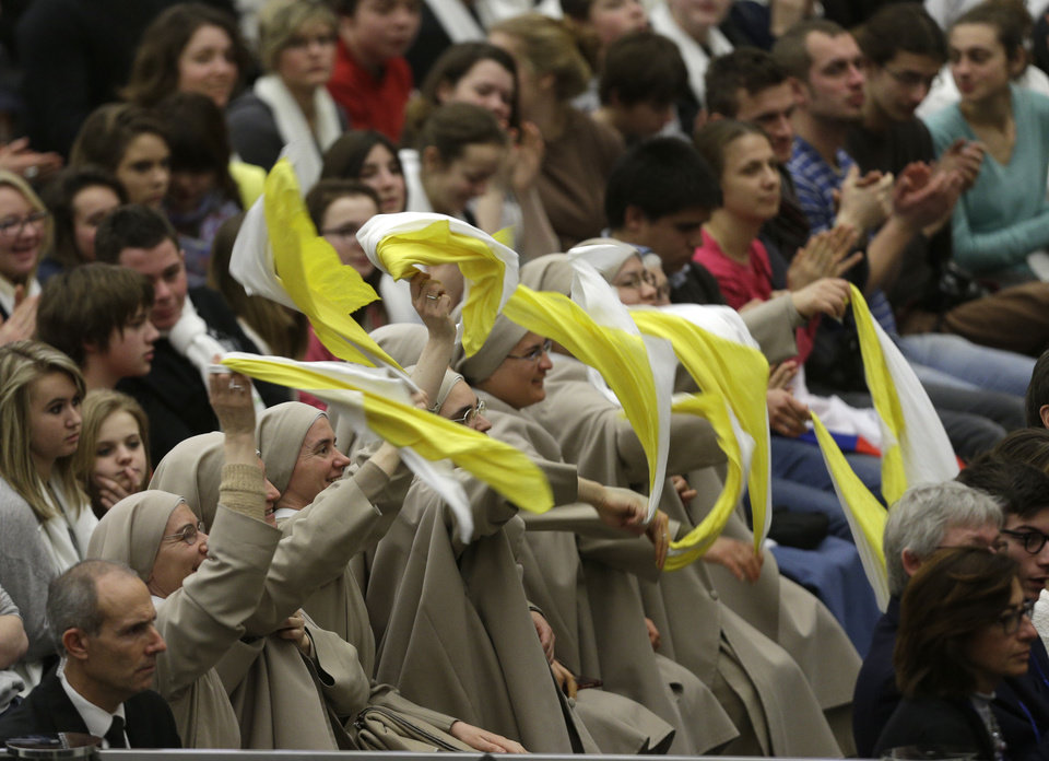 "Nuns cheer during Pope Benedict XVI's weekly general audience in the Paul VI Hall at the Vatican, Wednesday Feb. 13, 2013. Looking tired but serene, Pope Benedict XVI told thousands of faithful Wednesday that he was stepping down for ""the good of the church,"" speaking in his first public appearance since dropping the bombshell announcement of his resignation. The 85-year-old Benedict basked in more than a minute-long standing ovation when he entered the packed audience hall for his traditional Wednesday general audience. He was interrupted by applause by the thousands of people, many of whom had tears in their eyes. (AP Photo/Alessandra Tarantino)"