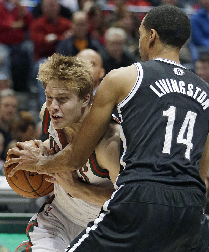 Photo - Milwaukee Bucks' Nate Wolters tries to drive past Brooklyn Nets' Shaun Livingston (14) during the second half of an NBA basketball game Saturday, Dec. 7, 2013, in Milwaukee. (AP Photo/Morry Gash)