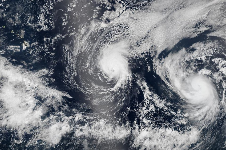 Photo - This Aug. 5, 2014 satellite image provided by NASA shows two tropical Pacific Ocean hurricanes - Iselle at center and Julio at right - bearing down on Hawaii, top left. Hurricane Iselle is expected to reach Hawaii Thursday night, Aug. 7, 2014. Tracking close behind it is Hurricane Julio, which strengthened early Thursday into a Category 2 storm. (AP Photo/NASA)