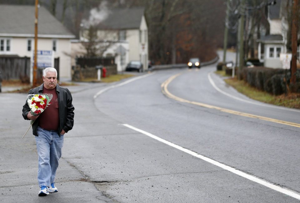 A man walks with flowers in the Sandy Hook village of Newtown, Conn., as the town mourns victims killed in a school shooting, Monday, Dec. 17, 2012. Authorities say a gunman killed his mother at their home and then opened fire inside the Sandy Hook Elementary School in Newtown, killing 26 people, including 20 children, before taking his own life, on Friday. (AP Photo/Julio Cortez)