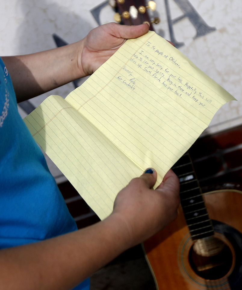 Photo - Volunteer Shelby Hays reads a note left on a donated guitar outside the Plaza Towers neighborhood in Moore, Okla., on Wednesday, May 22, 2013.A tornado damaged the area on Monday, May 20, 2013. Photo by Bryan Terry, The Oklahoman