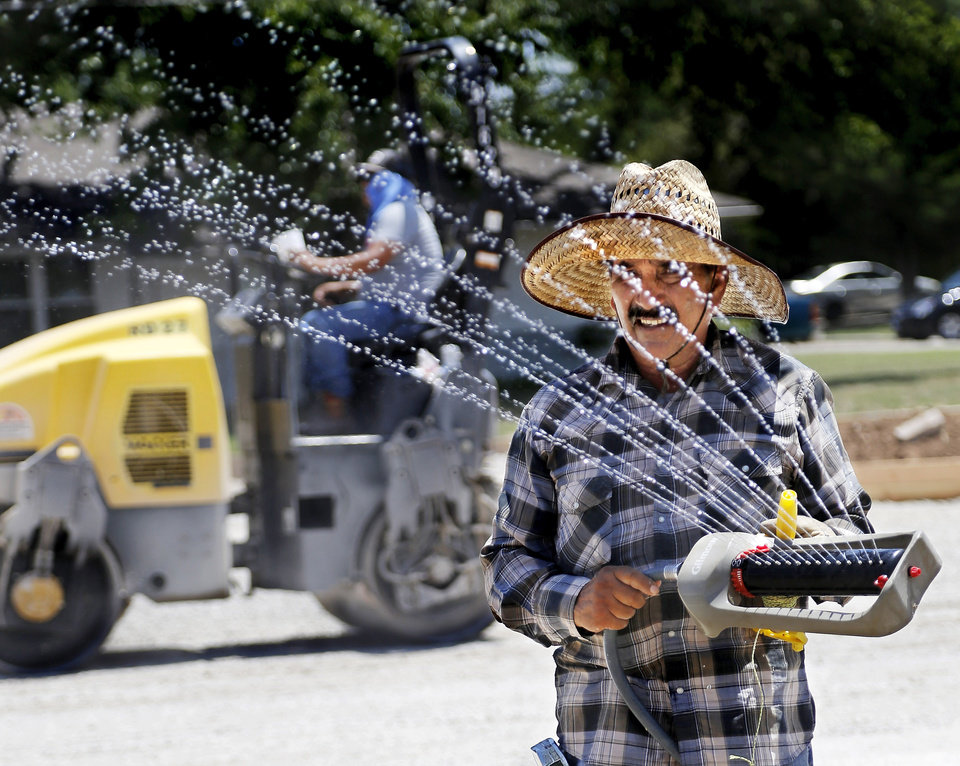Photo -  An employee of JC Concrete moves a sprinkler in the heat Wednesday as he and fellow crew members prepare the surface for a new parking lot on the south side of St. James the Greater Catholic Church near SW 44 and McKinley Avenue. [Photo by Jim Beckel, The Oklahoman]