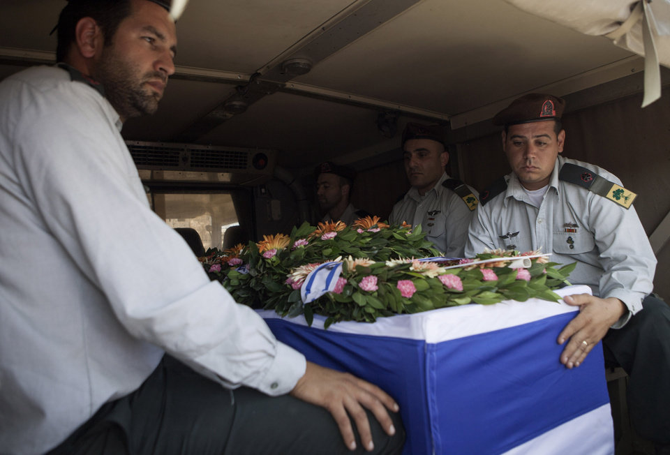 Photo - Israeli soldiers escort the coffin of Maj. Tzafrir Bar-Or, 32, one of 13 soldiers killed in several separate incidents in Shijaiyah on Sunday, at the military cemetery in Holon, Israel, Monday, July 21, 2014. On Sunday, the first major ground battle in two weeks of Israel-Hamas fighting exacted a steep price, killing scores of Palestinians and more than a dozen Israeli soldiers and forcing thousands of terrified Palestinian civilians to flee their devastated Shijaiyah neighborhood, which Israel says is a major source for rocket fire against its civilians. (AP Photo/Dan Balilty)