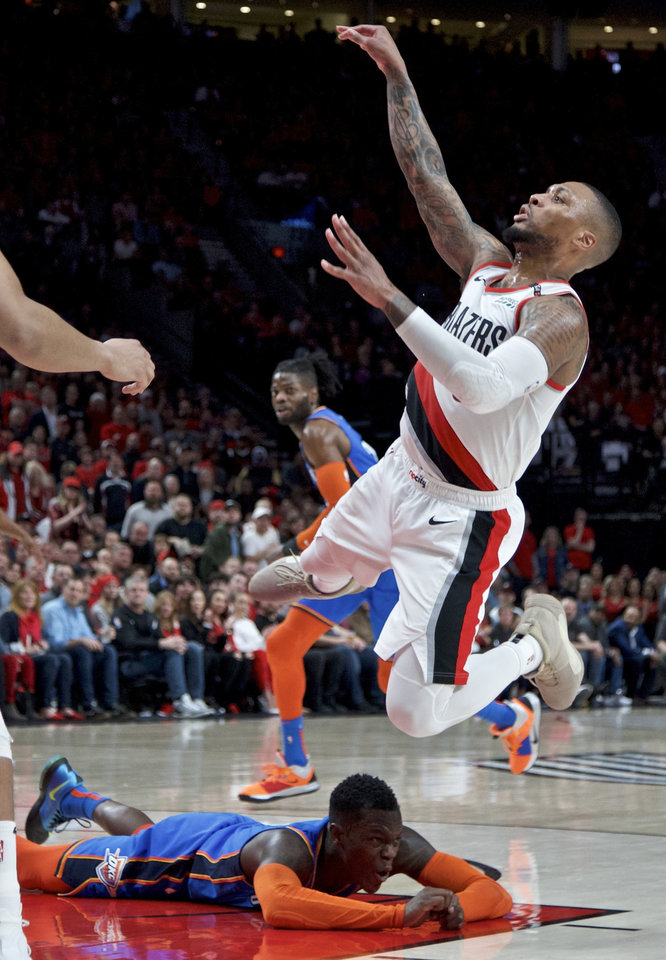 Photo - Portland Trail Blazers guard Damian Lillard, top, shoots after being fouled by Oklahoma City Thunder guard Dennis Schroeder, bottom, during the second half of Game 2 of an NBA basketball first-round playoff series Tuesday, April 16, 2019, in Portland, Ore. The Trail Blazers won 114-94. (AP Photo/Craig Mitchelldyer)