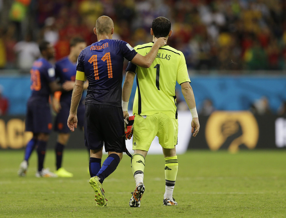 Photo - Netherlands' Arjen Robben walks with Spain's goalkeeper Iker Casillas after Netherlands' 5-1 victory over Spain during the group B World Cup soccer match between Spain and the Netherlands at the Arena Ponte Nova in Salvador, Brazil, Friday, June 13, 2014.  (AP Photo/Natacha Pisarenko)
