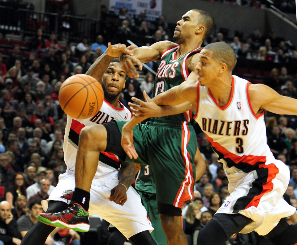 Photo - Milwaukee Bucks guard Ramon Sessions (13) has the ball knocked away by Portland Trail Blazers forward Thomas Robinson (41) and guard C.J. McCollum (3) during the first half of an NBA basketball game in Portland, Ore., Tuesday, March 18, 2014. (AP Photo/Steve Dykes)