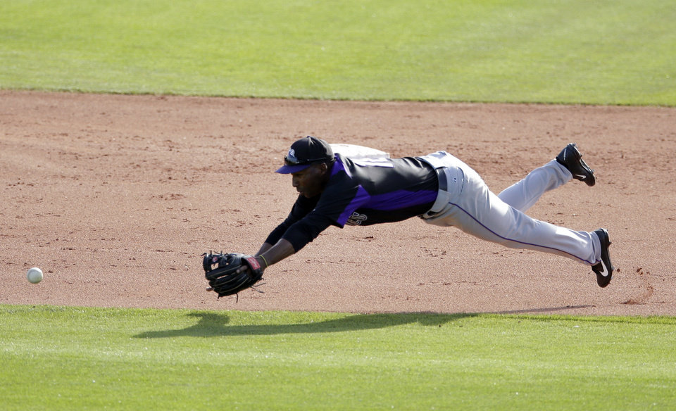 Photo - Colorado Rockies shortstop Jonathan Herrera leaps and misses a ball that went for a single by Kansas City Royals' Elliot Johnson during the eighth inning in a spring training baseball game Tuesday, March 19, 2013, in Surprise, Ariz. (AP Photo/Gregory Bull)