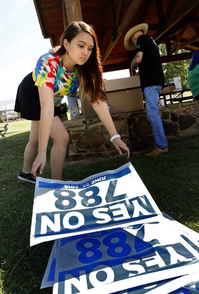 Photo - Jessi Hayes, University of Oklahoma student, and John Frasure, Norman, assemble campaign signs at a rally in support of State Question 788 at Andrews Park on Saturday, June 9, 2018 in Norman, Okla.  If passed it would authorize the medical use of marijuana.   Photo by Steve Sisney, The Oklahoman