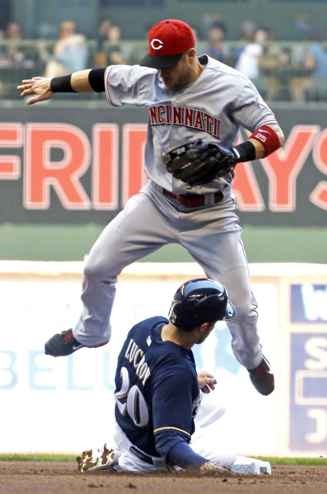 Photo - Cincinnati Reds' Skip Schumaker leaps over Milwaukee Brewers' Jonathan Lucroy (20) to complete a double play on a ball hit by Aramis Ramirez during the first inning of a baseball game Wednesday, July 23, 2014, in Milwaukee. (AP Photo/Morry Gash)