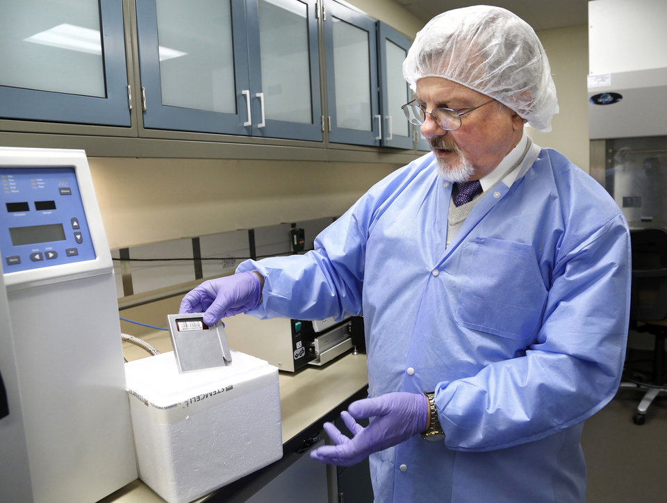 Photo - Dr.  James Smith, chief medical officer at the cord blood bank, places a cartridge that contains processed cord blood into a container in the cell processing room. Oklahoma Blood Institute hosted the grand opening of its new Cord Blood Bank Tuesday afternoon, Jan. 28, 2014. It is one of only 24 such centers worldwide. Umbilical cord blood that potentially can save lives has been thrown away after the births of babies across our state in the past. . Without a local public umbilical cord blood bank, most Oklahoma mothers have no option to donate it. Now, families at OU Medical Center, celebrating a joyous event in their own lives can bring the same to those battling leukemia and other blood disorders with little hope. Other hospitals will be enlisted to partner in the future.     Photo by Jim Beckel, The Oklahoman