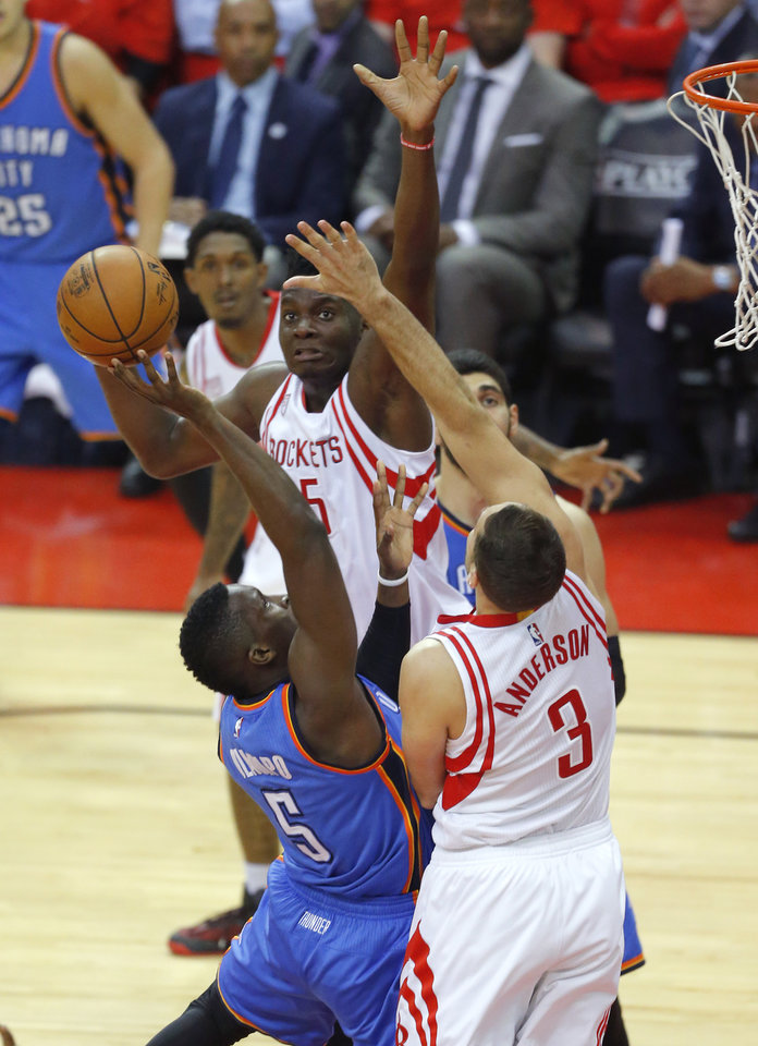 Photo - Oklahoma City's Victor Oladipo (5) tries to get a shot over Houston's Ryan Anderson (3) and Clint Capela (15) during Game 5 in the first round of the NBA playoffs between the Oklahoma City Thunder and the Houston Rockets at the Toyota Center in Houston, Texas,  Tuesday, April 25, 2017.  Photo by Sarah Phipps, The Oklahoman