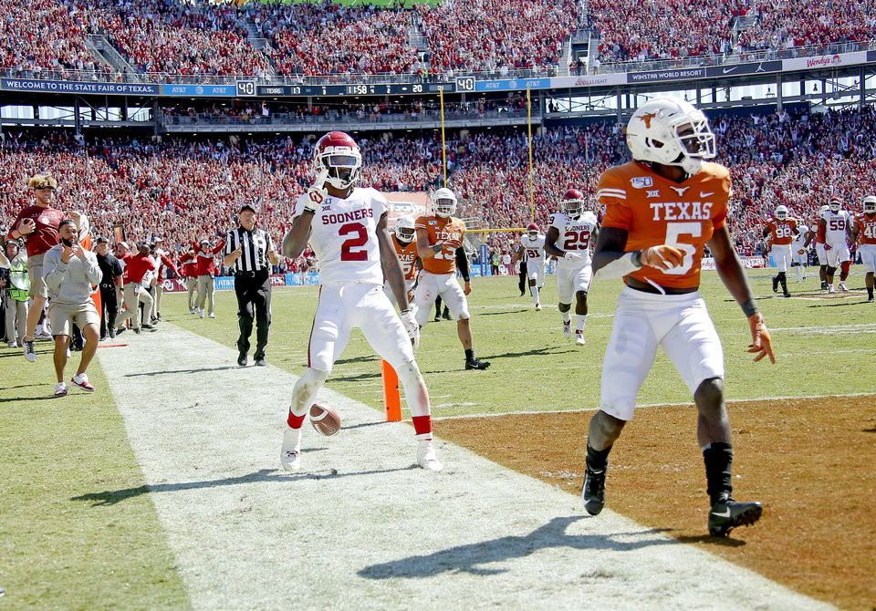 Photo - Oklahoma's CeeDee Lamb (2) celebrates his touchdown next to Texas defensive back D'Shawn Jamison (5) in the fourth quarter during the Red River Showdown college football game between the University of Oklahoma Sooners (OU) and the Texas Longhorns (UT) at Cotton Bowl Stadium in Dallas, Saturday, Oct. 12, 2019. OU won 34-27. [Sarah Phipps/The Oklahoman]