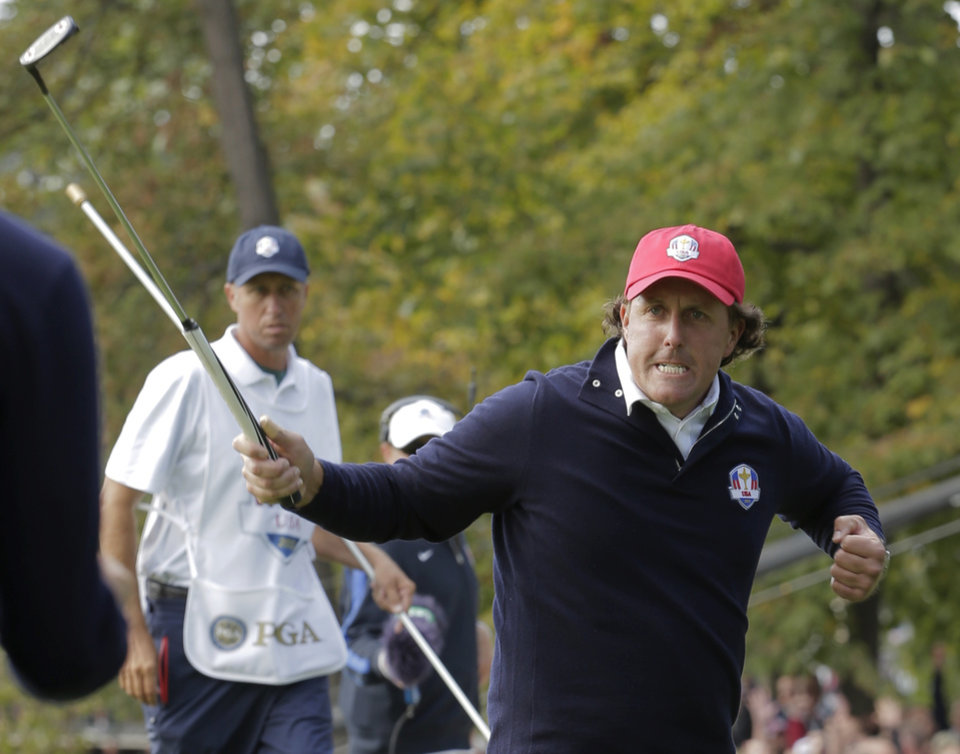 Photo -   USA's Phil Mickelson reacts after making a putt to win the 13th hole during a foresomes match at the Ryder Cup PGA golf tournament Friday, Sept. 28, 2012, at the Medinah Country Club in Medinah, Ill. (AP Photo/Charlie Riedel)