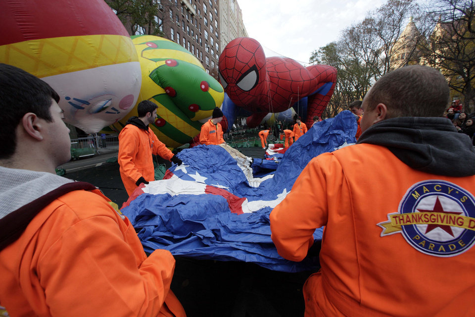 Photo -   Macy's workers unfold a balloon to be inflated for the 86th annual Macy's Thanksgiving Day Parade, adjacent to the Chloe and Spider-Man balloons, on New York's Upper West Side, Wednesday, Nov. 21, 2012. More than 3 million people typically attend the event and it has a TV audience of 50 million. (AP Photo/Richard Drew)
