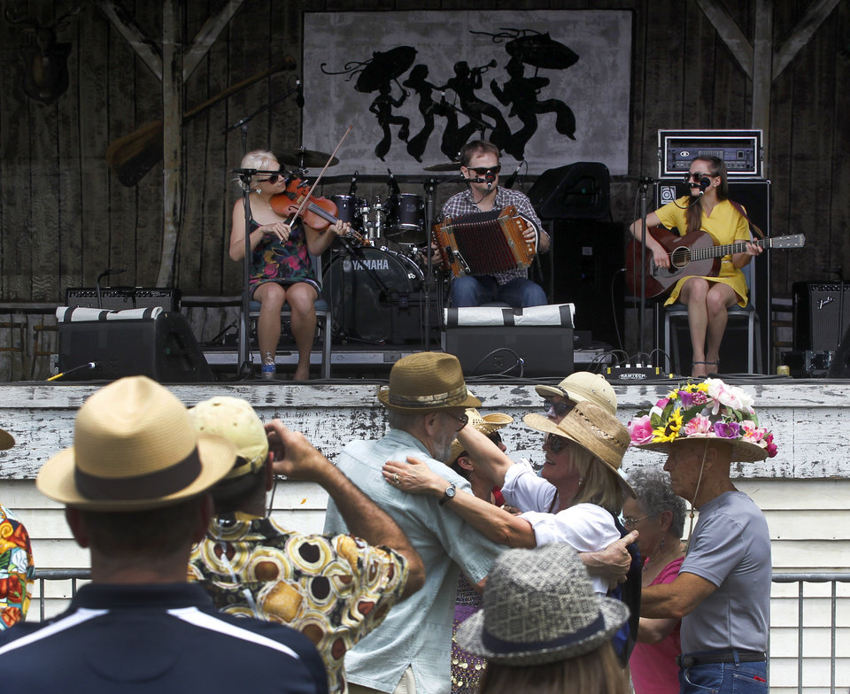 Photo - Festival-goers dance to the music of the Cajun band T'Monde, at the Fais Do Do stage during the New Orleans Jazz and Heritage Festival in New Orleans, Friday, April 26, 2013. The band members, from left, are Kelli Jones-Savoy on fiddle, Drew Simon on accordion, and Megan Brown on guitar. (AP Photo/Doug Parker)