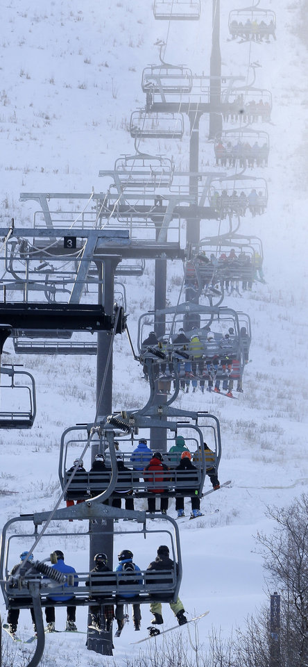 Photo - FILE - In this Nov. 23, 2013, file photo, skiers and snowboarders ride a lift at Park City Mountain Resort, in Park City, Utah. A long-running court battle between two ski industry titans is putting the upcoming season in jeopardy at one of Utah's largest resorts. A Utah judge is expected to decide Friday how much Park City Mountain Resort must pay to cover back rent and court costs so it can stay open through April 2015. If the price tag is too high, the lifts could stand idle when the season opens in less than three months. (AP Photo/Rick Bowmer, File)