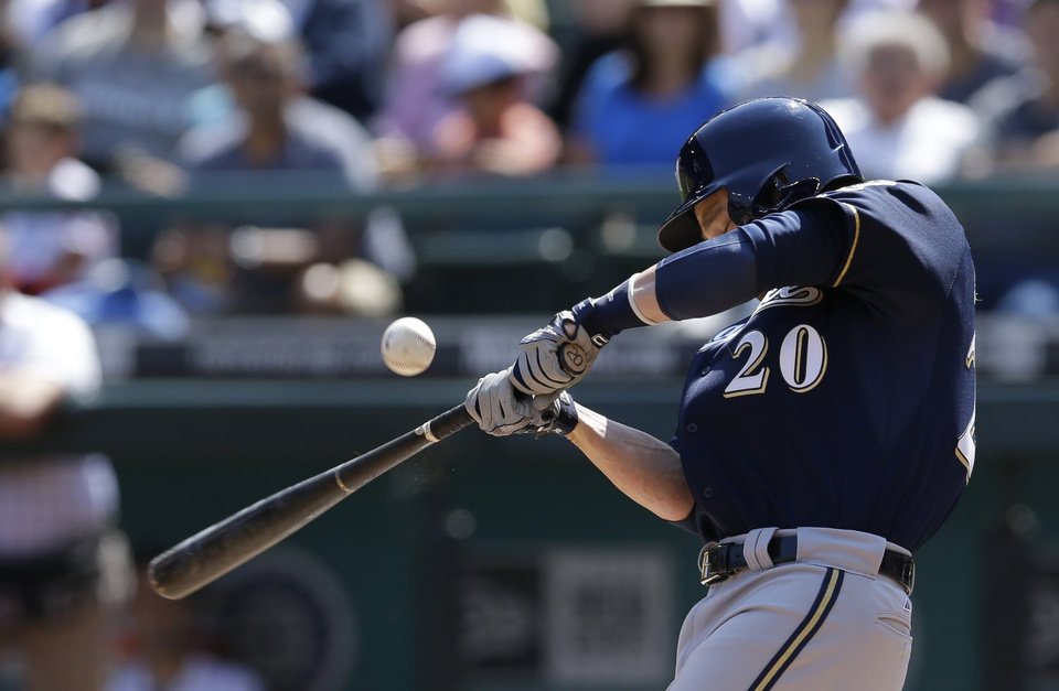 Photo - Milwaukee Brewers' Jonathan Lucroy pops out to foul territory during an at-bat in the first inning of a baseball game against the Seattle Mariners, Sunday, Aug. 11, 2013, in Seattle. (AP Photo/Ted S. Warren)