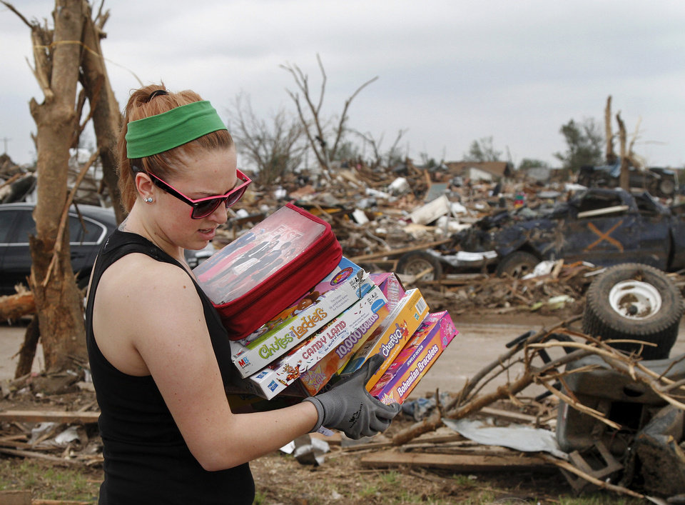 Photo - Ashton Forston carries board games she found in the rubble of Trina Minnick's home at 936 SW 15. Forston showed up in the neighborhood with her boyfriend and her mom, and another man. They spent several hours going through the remains of Minnick's house, rescuing plastic tubs filled with family keepsakes, photo albums and mementos. Minnick said resolutely,