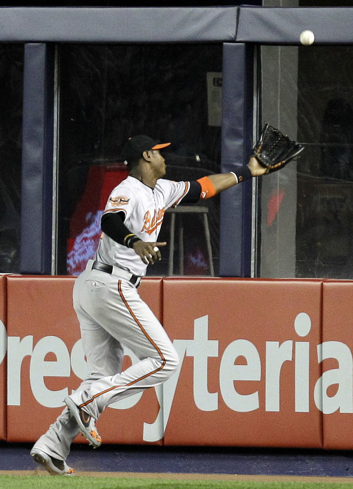 Photo -   Baltimore Orioles center fielder Adam Jones chases an RBI triple by New York Yankees' Derek Jeter during the third inning in Game 3 of the American League division baseball series Wednesday, Oct. 10, 2012, in New York. (AP Photo/Kathy Willens)