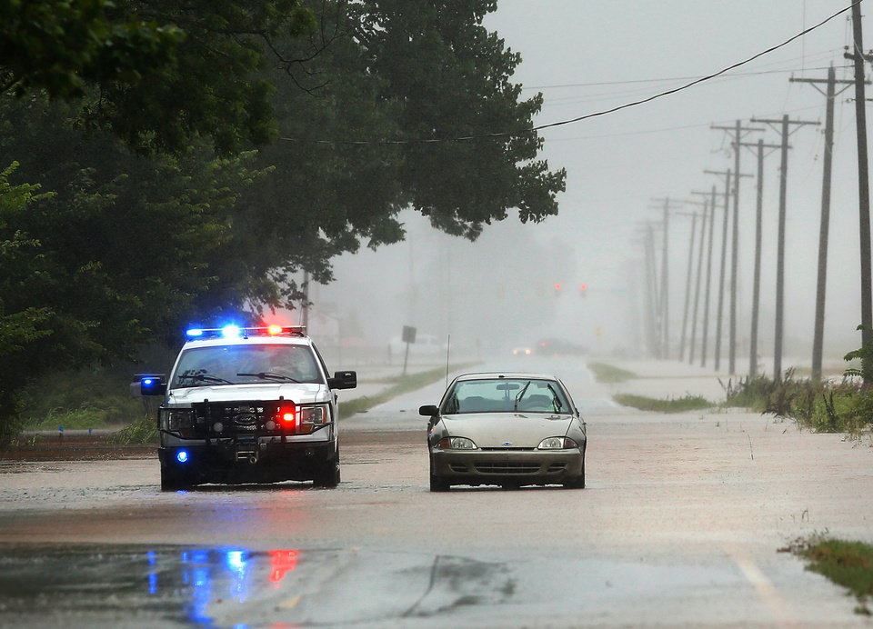 Photo - A Citizen Potawatomi Nation police vehicle pulls alongside this abandoned car along a section of Hardesy Road in Shawnee that had been flooded less than an hour earlier when rain from Hurricane Bill produced localized flooding in areas of Pottawatomie County on Thursday, June 18,  2015.    Photo by Jim Beckel, The Oklahoman.