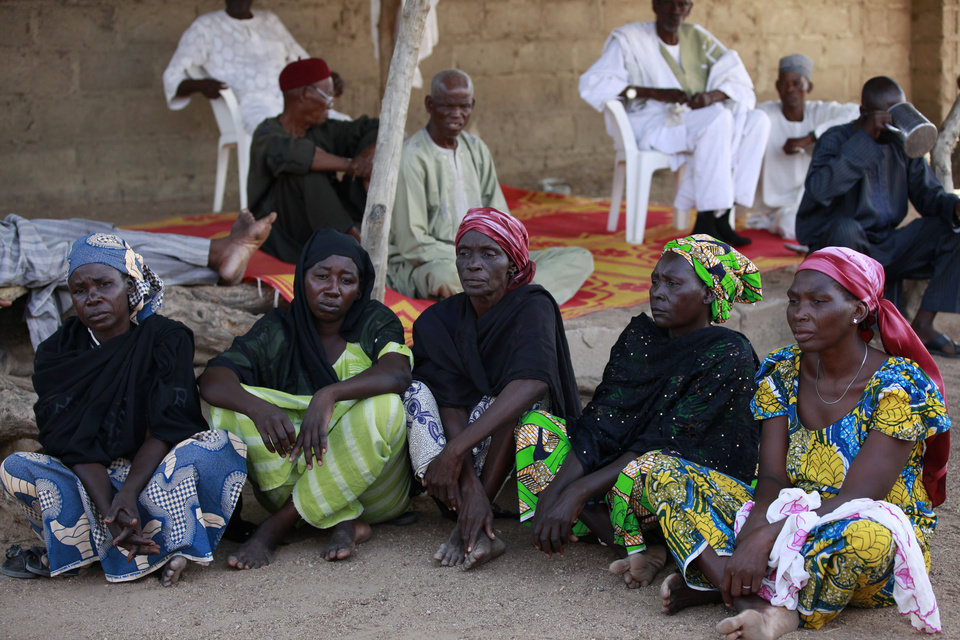 Photo - FILE- In this Sunday, May 18, 2014 file photo some of the parents of the kidnapped school girls sit outside a compound during a meeting in Chibok, Nigeria. At least 11 parents of the more than 200 kidnapped Nigerian schoolgirls will never see their daughters again. Since the mass abduction of the schoolgirls by Islamic extremists three months ago, at least 11 of their parents have died and their hometown, Chibok, is under siege from the militants, residents report. Seven fathers of kidnapped girls were among 51 bodies brought to Chibok hospital after an attack on the nearby village of Kautakari this month, said a health worker who insisted on anonymity for fear of reprisals by the extremists. At least four more parents have died of heart failure, high blood pressure and other illnesses that the community blames on trauma due to the mass abduction 100 days ago, said community leader Pogu Bitrus, who provided their names.  (AP Photo/Sunday Alamba, File)