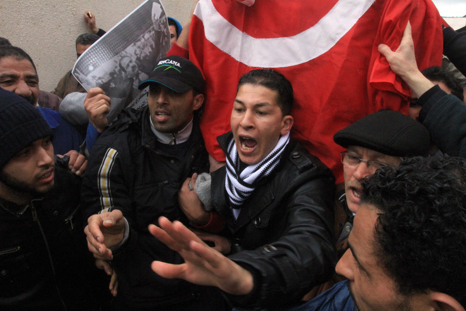Photo - Relatives of slain opposition leader Chokri Belaid carry the coffin wrapped in the Tunisian red flag during his funeral in Tunis, Friday, Feb. 8, 2013. Tunisia braced for clashes on Friday, with the capital shut down by a general strike and the army deployed for the funeral of a slain opposition leader expected to draw tens of thousands of mourners, and potentially many more. (AP Photo/Amine Landoulsi)