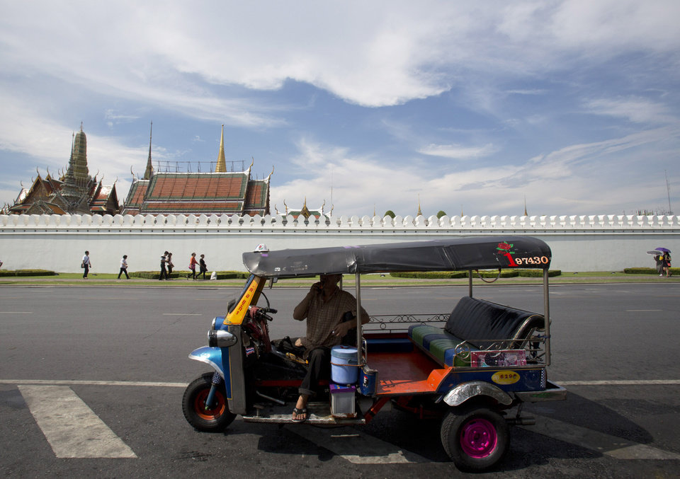 Photo - A motor tricycle driver, foreground, waits for customer as foreign tourists, background, walk near the wall of the Grand Palace during a tour Tuesday, May 27, 2014 in Bangkok, Thailand. For Thailand's tourist industry, the situation is more ominous. Bookings were already down after six months of anti-government protests in Bangkok, and the combination of coup plus curfew along with uncertainty over how long the crackdown will last could be bruising, hotels and industry experts say. It's a blow the economy, already struggling, could do without. (AP Photo/Sakchai Lalit)