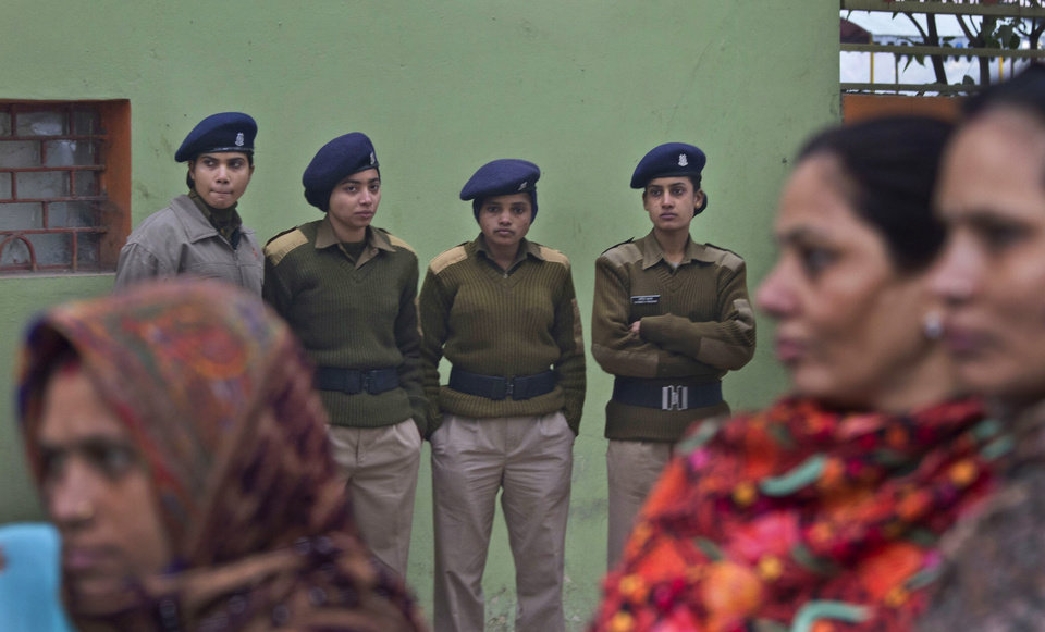Photo - Female Indian paramilitary soldiers watch as Indian women march to mourn the death of a gang rape victim in New Delhi, India, Wednesday, Jan. 2, 2013. India's top court said it will decide whether to suspend lawmakers facing sexual assault charges as thousands of women gathered at the memorial to independence leader Mohandas K. Gandhi to demand stronger protection for their safety. (AP Photo/ Dar Yasin)