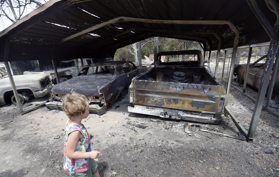 Abigail Bell looks at a relative's burned cars , Sunday, Aug. 5, 2012, in the community of Oak Grove, Okla., after wildfires moved through the area Saturday. Photo by Sarah Phipps, The Oklahoman