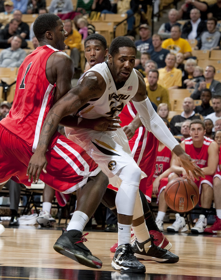 Missouri's Alex Oriakhi, right, tries to dribble around Southeast Missouri State's Nino Johnson, left, as Southeast Missouri State's Tyler Stone, back, watches during the first half of an NCAA college basketball game Tuesday, Dec. 4, 2012, in Columbia, Mo. (AP Photo/L.G. Patterson)