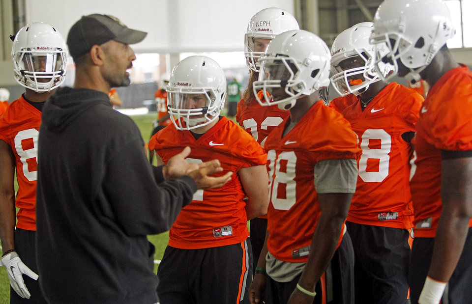 Photo - Oklahoma State receivers coach Kasey Dunn instructs the team on how to catch a football during the first team practice of the fall at the Sherman E. Smith Training Facility on the campus of Oklahoma State University in Stillwater on August 1, 2014. Photo by KT King, The Oklahoman