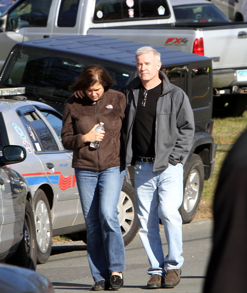 Photo - Parents walk away from the Sandy Hook Elementary School in Newtown, Conn. where authorities say a gunman opened fire, leaving 27 people dead, including 20 children, Friday, Dec. 14, 2012. (AP Photo/The Journal News, Frank Becerra Jr.) MANDATORY CREDIT, NYC OUT, NO SALES, TV OUT, NEWSDAY OUT; MAGS OUT ORG XMIT: NYWHI113