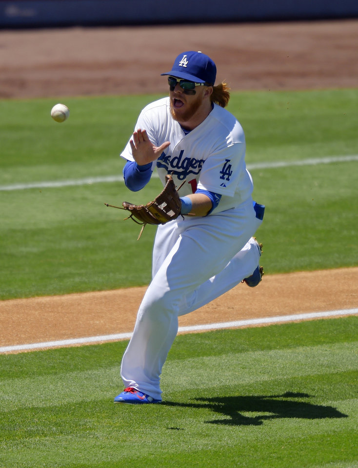 Photo - Los Angeles Dodgers third baseman Justin Turner makes a catch on a ball hit by Milwaukee Brewers' Wily Peralta during the second inning of a baseball game, Sunday, Aug. 17, 2014, in Los Angeles. (AP Photo/Mark J. Terrill)