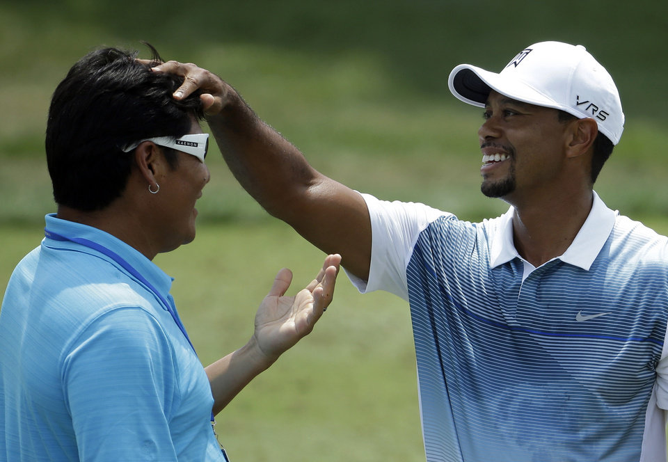 Photo - Tiger Woods, right, greets long time friend Notah Begay on the driving range before practice round for the PGA Championship golf tournament at Valhalla Golf Club on Wednesday, Aug. 6, 2014, in Louisville, Ky. The tournament is set to begin on Thursday. (AP Photo/Jeff Roberson)