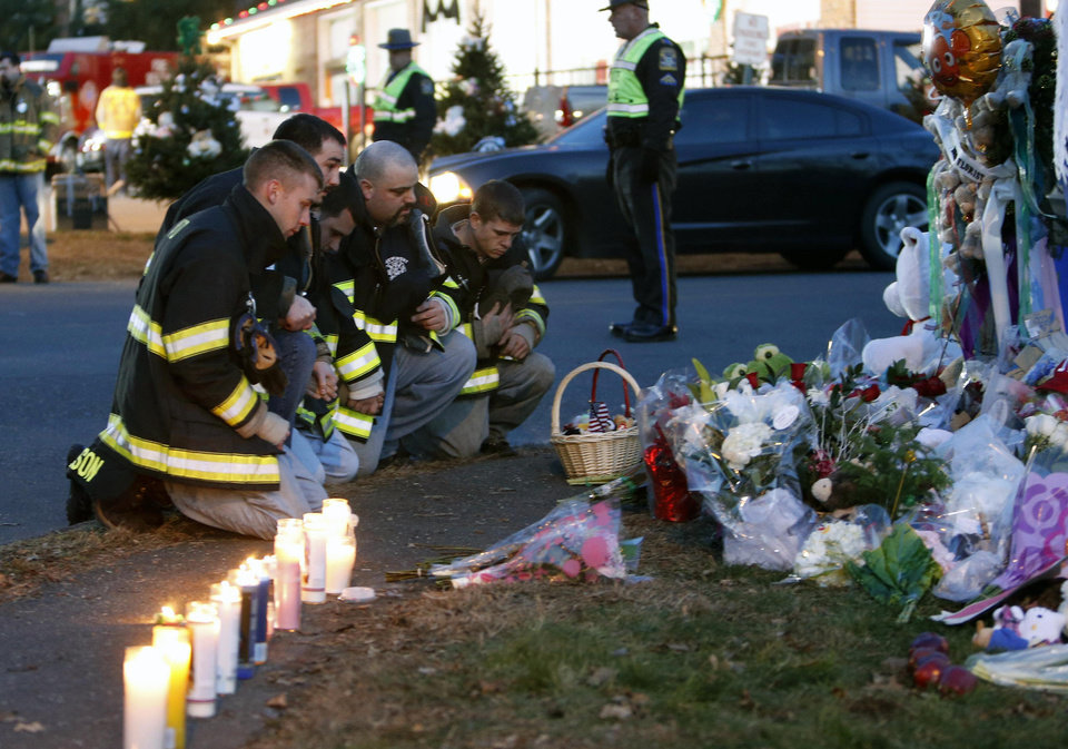 Photo - Firefighters pay their respects at a memorial for shooting victims near Sandy Hook Elementary School, Saturday, Dec. 15, 2012 in Newtown, Conn.  A gunman walked into Sandy Hook Elementary School in Newtown Friday and opened fire, killing 26 people, including 20 children. (AP Photo/Jason DeCrow) ORG XMIT: CTJD116