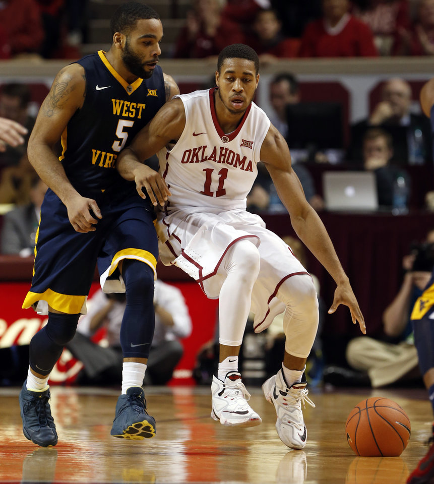 Photo - Oklahoma's Isaiah Cousins (11) is fouled by West Virginia's Jaysean Paige (5) as the University of Oklahoma Sooner (OU) men play the West Virginia Mountaineers (WV) in NCAA, college basketball at The Lloyd Noble Center on Jan. 16, 2016 in Norman, Okla. Photo by Steve Sisney, The Oklahoman