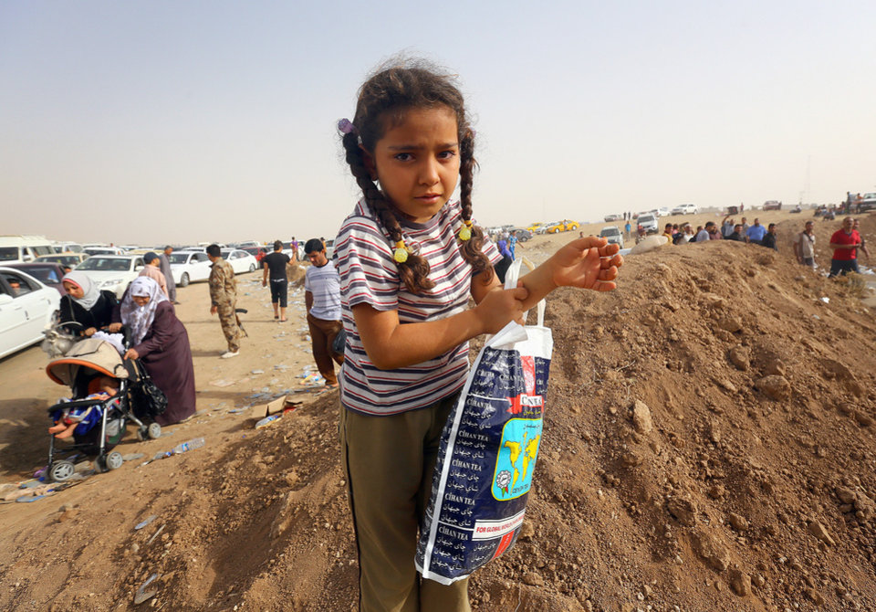 Photo - Refugees fleeing from Mosul head to the self-ruled northern Kurdish region in Irbil, Iraq, 350 kilometers (217 miles) north of Baghdad, Thursday, June 12, 2014. The Islamic State of Iraq and the Levant, the al-Qaida breakaway group, on Monday and Tuesday took over much of Mosul in Iraq and then swept into the city of Tikrit further south. An estimated half a million residents fled Mosul, the economically important city. (AP Photo)
