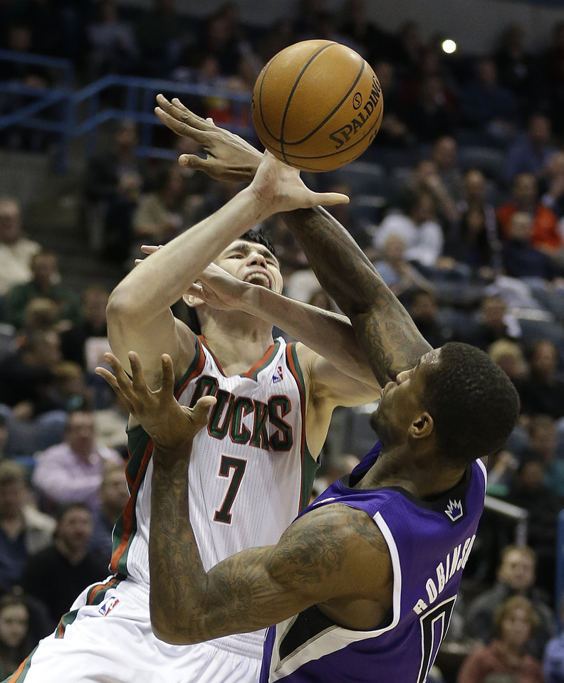 Milwaukee Bucks\' Ersan Ilyasova (7) is fouled by Sacramento Kings\' Thomas Robinson, right, during the second half of an NBA basketball game on Wednesday, Dec. 12, 2012, in Milwaukee. (AP Photo/Jeffrey Phelps)