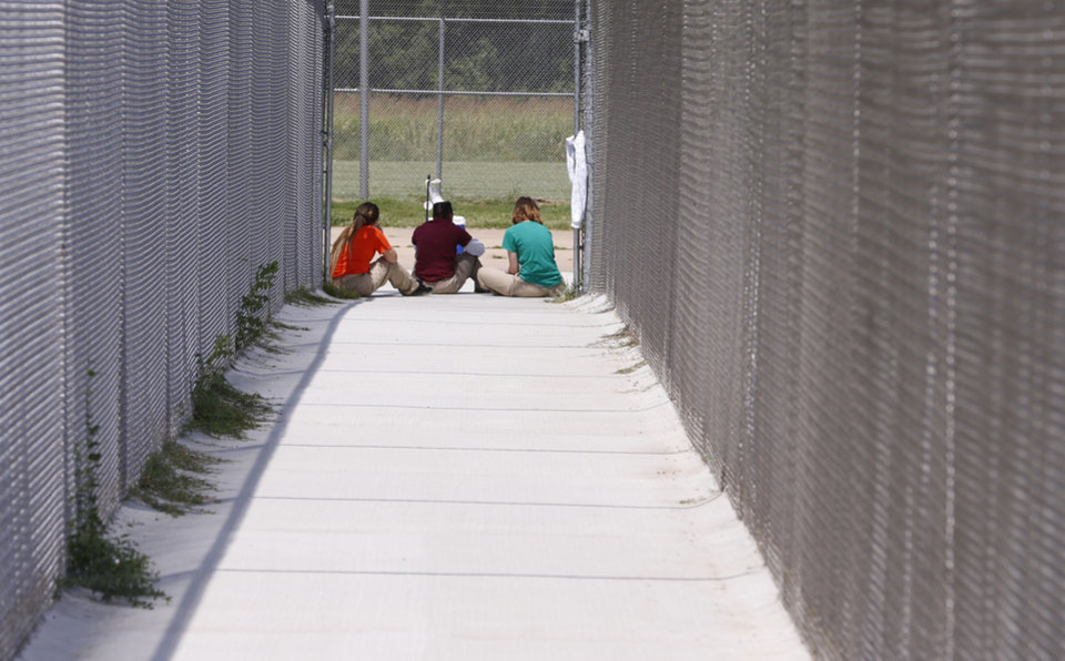 Photo -  Girls in state custody sit in the only outdoor space available to them, a fenced-in basketball court, at the Oklahoma Juvenile Center for Girls in Norman. [Photo by Steve Sisney, The Oklahoman]