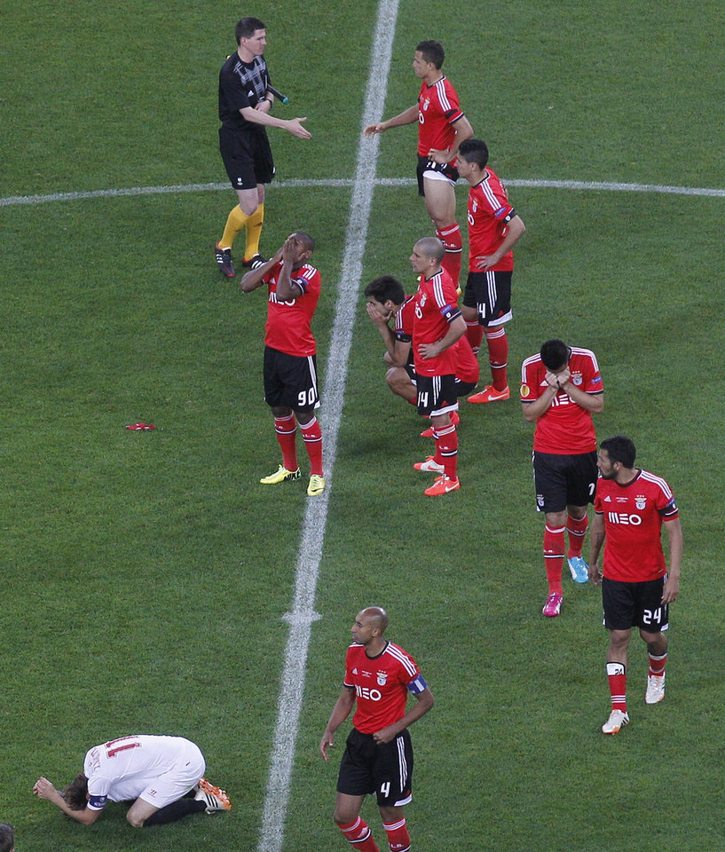 Photo - Sevilla's Ivan Rakitic, centre, sinks to his knees in celebration as his team win a penalty shoot out at the end of the Europa League soccer final between Sevilla and Benfica, at the Turin Juventus stadium in Turin, Italy, Wednesday, May 14, 2014. Sevilla beat Benfica 4-2 on penalties to win Europa League final. (AP Photo/Luca Bruno)
