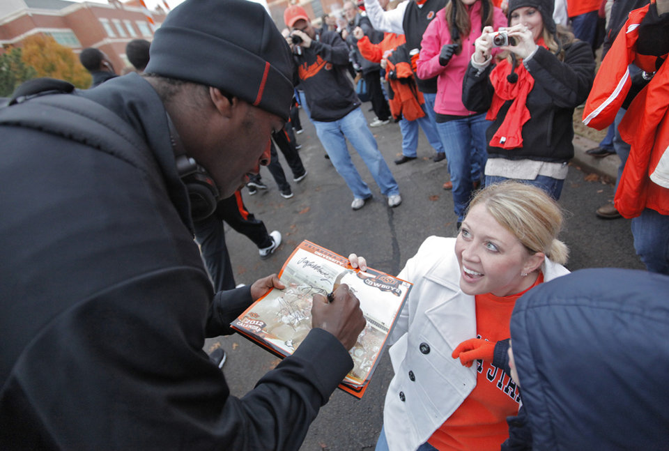 Photo - Heidi Wilburn reacts as she gets an autograph from Justin Blackmon in the 'Spirit Walk' before the Bedlam college football game between the Oklahoma State University Cowboys (OSU) and the University of Oklahoma Sooners (OU) at Boone Pickens Stadium in Stillwater, Okla., Saturday, Dec. 3, 2011. Photo by Chris Landsberger, The Oklahoman